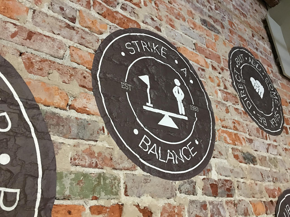 trinity graphic tackles a brick wall installation sign builder